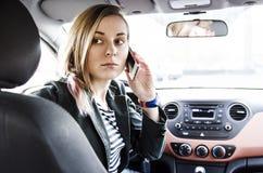 Schöne junge attraktive Frau, die im Fahrersitz sitzt Stockfotos