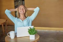 Schöne junge auf Arbeitsplatz mit Laptop sitzende und entspannende Frau Stockfotografie