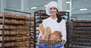 Schöne junge Bäckerdame, die einen frischen Weinlesekorb mit organischem Brot hält und gerade zur Kamera schaut und stock video footage