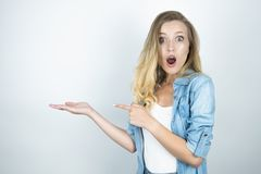 Schöne junge blonde überraschte Frauenvertretungsrichtung mit beiden Händen nah herauf weißen Hintergrund stockfotos