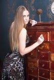Schöne junge blonde behaarte Frau öffnet Fach Lizenzfreie Stockfotografie
