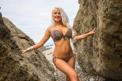Schöne junge blonde behaarte Frau stand zwischen zwei Felsen in b Lizenzfreie Stockbilder
