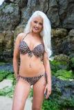 Schöne junge blonde behaarte Frau am Strand beim Bikinilächeln Stockfoto