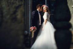 Schöne junge blonde Braut im weißen Kleid mit hübschem Bräutigam Lizenzfreie Stockfotografie