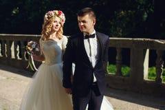 Schöne junge blonde Braut im weißen Kleid mit hübschem Bräutigam Lizenzfreies Stockfoto