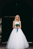 Schöne junge blonde Braut mit Brautblumenstrauß steht über altem Bogen Lizenzfreie Stockfotografie