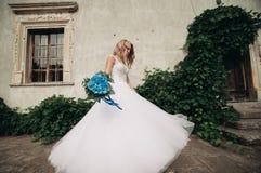 Schöne junge blonde Braut mit Brautblumenstraußtanzen auf den herrlichen Anlagen des Hintergrundes Lizenzfreie Stockfotos