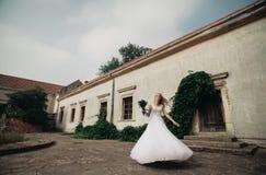 Schöne junge blonde Braut mit Brautblumenstraußtanzen auf den herrlichen Anlagen des Hintergrundes Stockfotografie