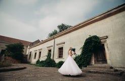 Schöne junge blonde Braut mit Brautblumenstraußtanzen auf den herrlichen Anlagen des Hintergrundes Stockfotos