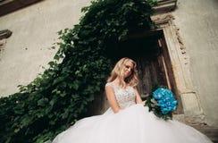 Schöne junge blonde Braut mit dem Brautblumenstrauß, der auf den herrlichen Anlagen des Treppenhintergrundes sitzt Lizenzfreies Stockbild