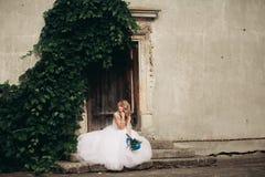 Schöne junge blonde Braut mit dem Brautblumenstrauß, der auf der Treppe auf den herrlichen Anlagen des Hintergrundes sitzt Lizenzfreies Stockfoto