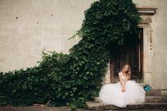 Schöne junge blonde Braut mit dem Brautblumenstrauß, der auf der Treppe auf den herrlichen Anlagen des Hintergrundes sitzt Lizenzfreie Stockfotos