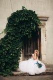 Schöne junge blonde Braut mit dem Brautblumenstrauß, der auf der Treppe auf den herrlichen Anlagen des Hintergrundes sitzt Stockbilder