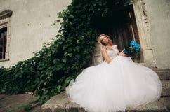 Schöne junge blonde Braut mit dem Brautblumenstrauß, der auf der Treppe auf den herrlichen Anlagen des Hintergrundes sitzt Stockfotografie