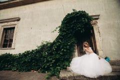 Schöne junge blonde Braut mit dem Brautblumenstrauß, der auf der Treppe auf den herrlichen Anlagen des Hintergrundes sitzt Stockbild