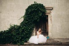 Schöne junge blonde Braut mit dem Brautblumenstrauß, der auf der Treppe unter herrlichen Anlagen sitzt Stockfoto