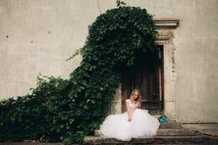 Schöne junge blonde Braut mit dem Brautblumenstrauß, der auf der Treppe unter herrlichen Anlagen sitzt Stockfotos