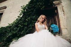 Schöne junge blonde Braut mit dem Brautblumenstrauß, der auf der Treppe unter herrlichen Anlagen sitzt Lizenzfreies Stockfoto