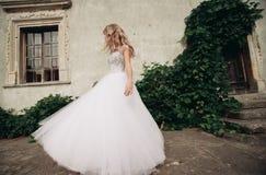 Schöne junge blonde Braut mit dem Brautblumenstrauß, der auf der Treppe unter herrlichen Anlagen sitzt Stockbilder