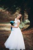 Schöne junge blonde Braut mit dem Brautblumenstrauß, der auf der Treppe unter herrlichen Anlagen sitzt Lizenzfreies Stockbild
