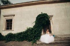 Schöne junge blonde Braut mit dem Brautblumenstrauß, der auf der Treppe unter herrlichen Anlagen sitzt Lizenzfreie Stockfotos