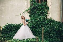 Schöne junge blonde Braut mit dem Brautblumenstrauß, der auf der Treppe unter herrlichen Anlagen sitzt Stockbild