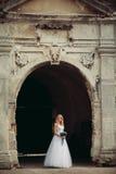 Schöne junge blonde Braut mit dem Brautblumenstrauß, der auf der Treppe unter herrlichen Anlagen sitzt Lizenzfreie Stockbilder