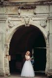 Schöne junge blonde Braut mit dem Brautblumenstrauß, der auf der Treppe unter herrlichen Anlagen sitzt Stockfotografie
