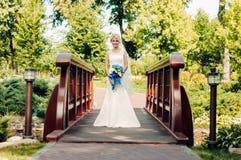 Schöne junge blonde Braut steht auf einer Brücke in einem exotischen Park Lizenzfreie Stockbilder