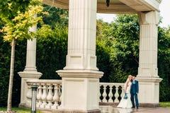 Schöne junge blonde Braut steht nahe bei dem Bräutigam in einem exotischen Park Lizenzfreie Stockfotos