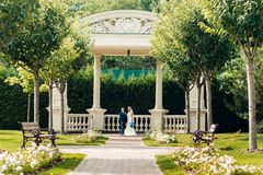 Schöne junge blonde Braut steht nahe bei dem Bräutigam in einem exotischen Park Stockfoto