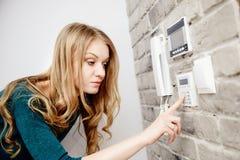 Schöne junge blonde Frau aktiviert eine Warnung im Haus Lizenzfreie Stockfotos