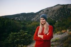 Schöne junge blonde Frau auf dem Hintergrund des Berges und des Waldes Stockbilder
