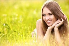 Schöne junge blonde Frau auf der Wiese Stockfoto