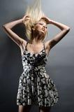 Schöne junge blonde Frau auf einem grauen Hintergrund Lizenzfreies Stockfoto