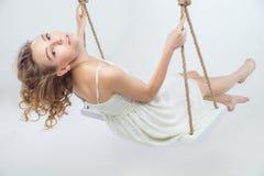 Schöne junge blonde Frau auf einem Schwingen Lizenzfreies Stockfoto