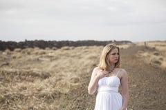 Schöne junge blonde Frau auf Strand mit weißem Kleid Lizenzfreie Stockfotografie