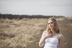 Schöne junge blonde Frau auf Strand mit weißem Kleid Stockfoto