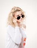 Schöne junge blonde Frau in den dunklen Gläsern und in der weißen Strickjacke Lizenzfreie Stockbilder