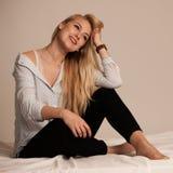 Schöne junge blonde Frau, die auf Bett stting ist Lizenzfreie Stockfotografie