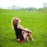 Schöne junge blonde Frau, die auf dem Gras sitzt. Stockbilder