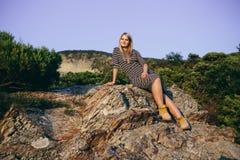Schöne junge blonde Frau, die auf dem Hintergrund von Bergen und von Wäldern sitzt Lizenzfreie Stockfotografie