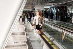 Schöne junge blonde Frau, die auf den beweglichen Gehwegen Innen steht Stockbild