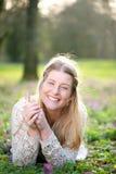 Schöne junge blonde Frau, die auf der Wiese liegt Lizenzfreies Stockbild