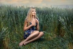 Schöne junge blonde Frau, die auf einem Gebiet des Weizens sitzt Lizenzfreie Stockbilder