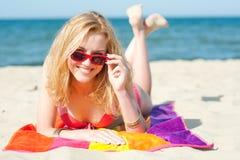 Schöne junge blonde Frau, die auf einem Strand liegt Stockfotos