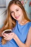 Schöne junge blonde Frau, die auf einer Couch, eine Schale von halten sitzt Lizenzfreies Stockbild