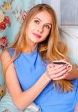 Schöne junge blonde Frau, die auf einer Couch, eine Schale von halten sitzt Stockfotografie