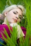 Schöne junge blonde Frau, die auf grünem Gras liegt Stockfotografie