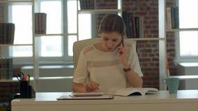 Schöne junge blonde Frau, die auf Handy und Lesebuch spricht Lizenzfreie Stockfotos